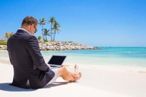 business man with a laptop on a beach in the sunshine, not normal business practice