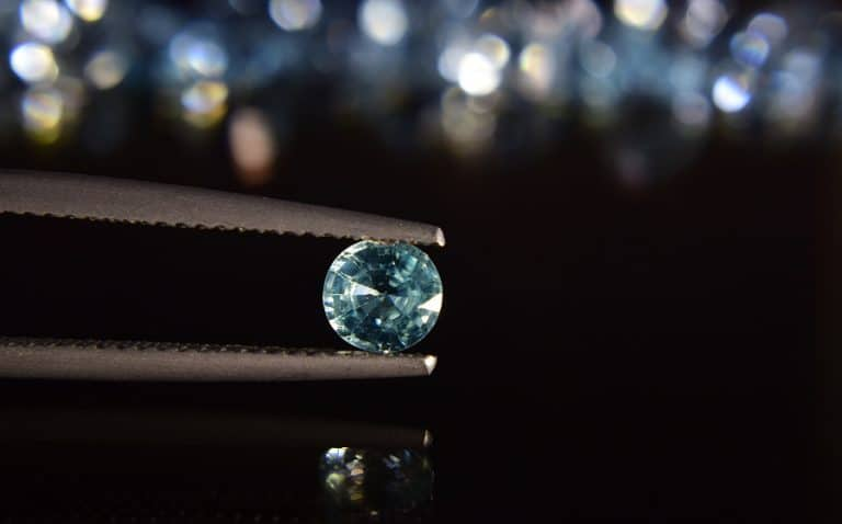 A diamond held in tweezers - in a pandemic are your the diamond or the coal?